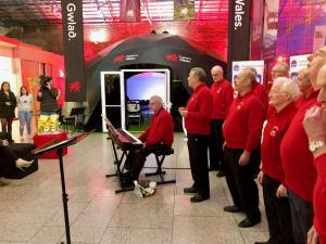 Dublin Welsh choir performing outside Dome Cymru